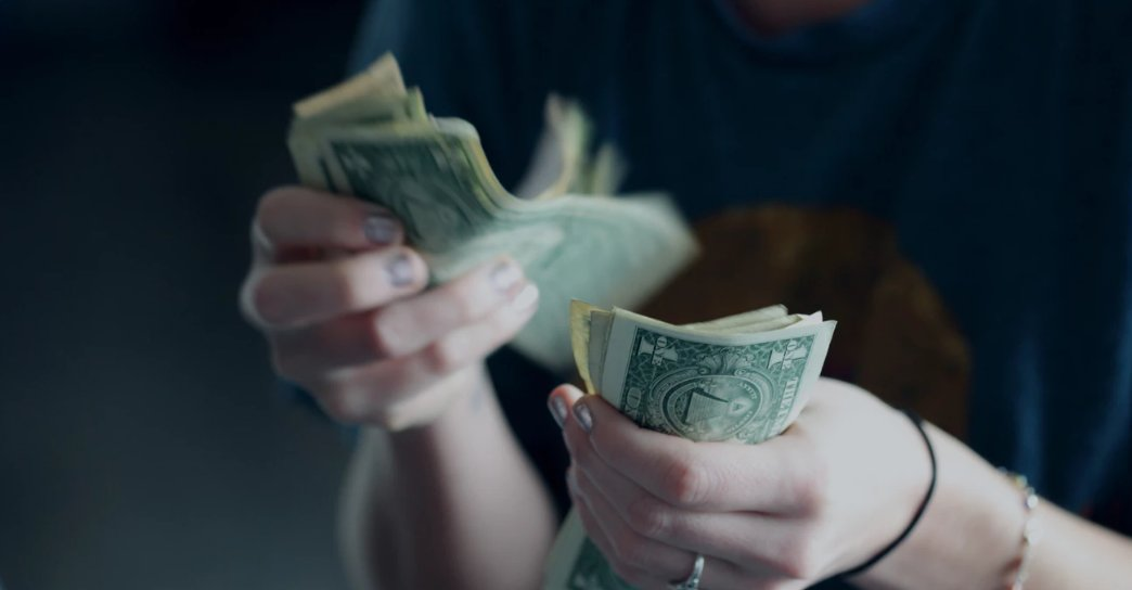 A female counting cash with both her hands