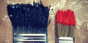 Two paintbrushes dipped in dark colored paint