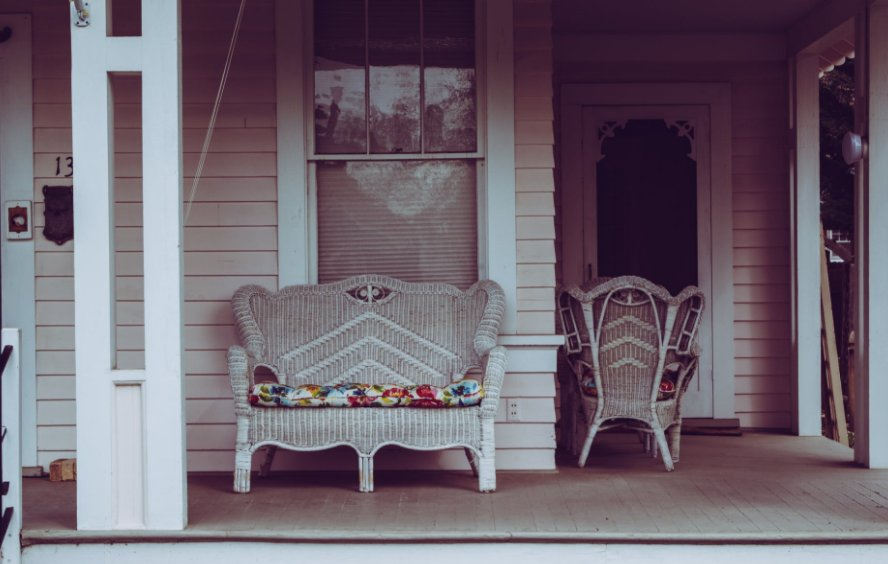 A porch with white chair furniture