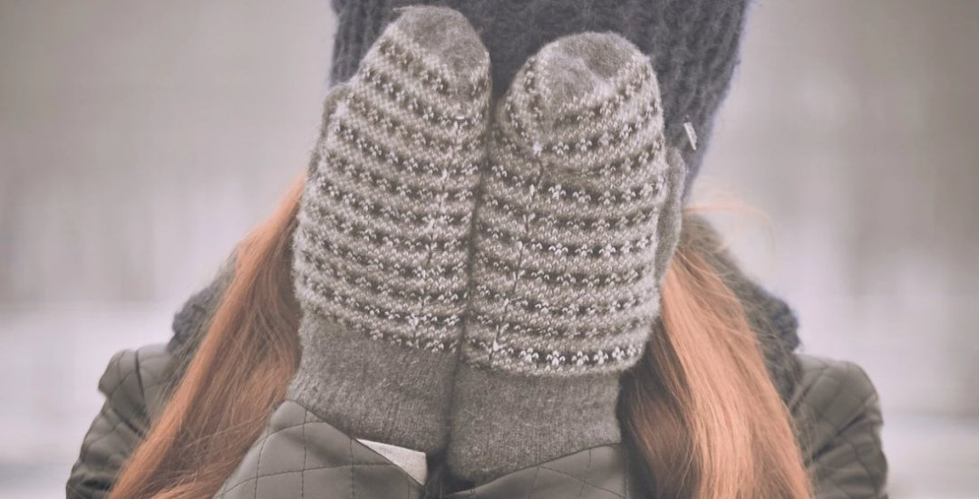 Woman covering her face with mittens in winter