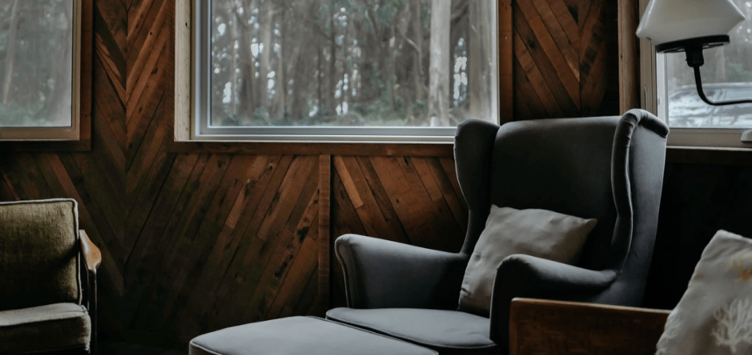 Cozy living room with wooden walls and comfy old couches and chairs