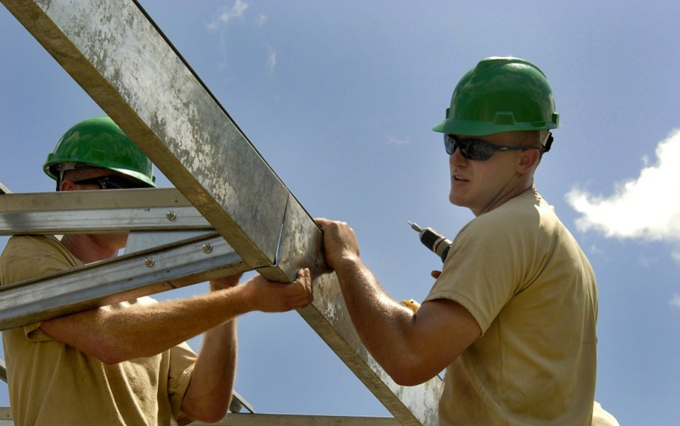 Two construction workers carrying beams
