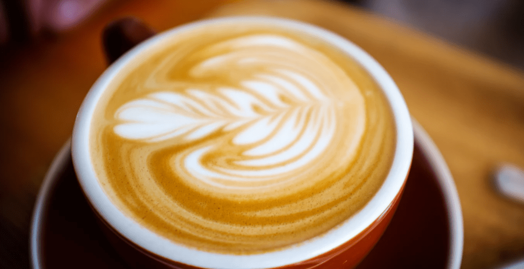 A cup of coffee with coffee art