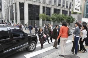 Veículo forçando a passagem em meio à travessia de pedestres