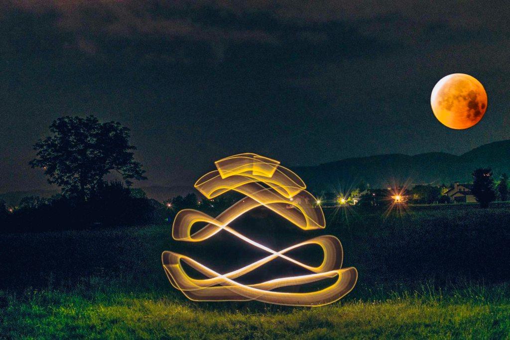 Fotomontage eines Lightpaintingbildes und des Blutmonds