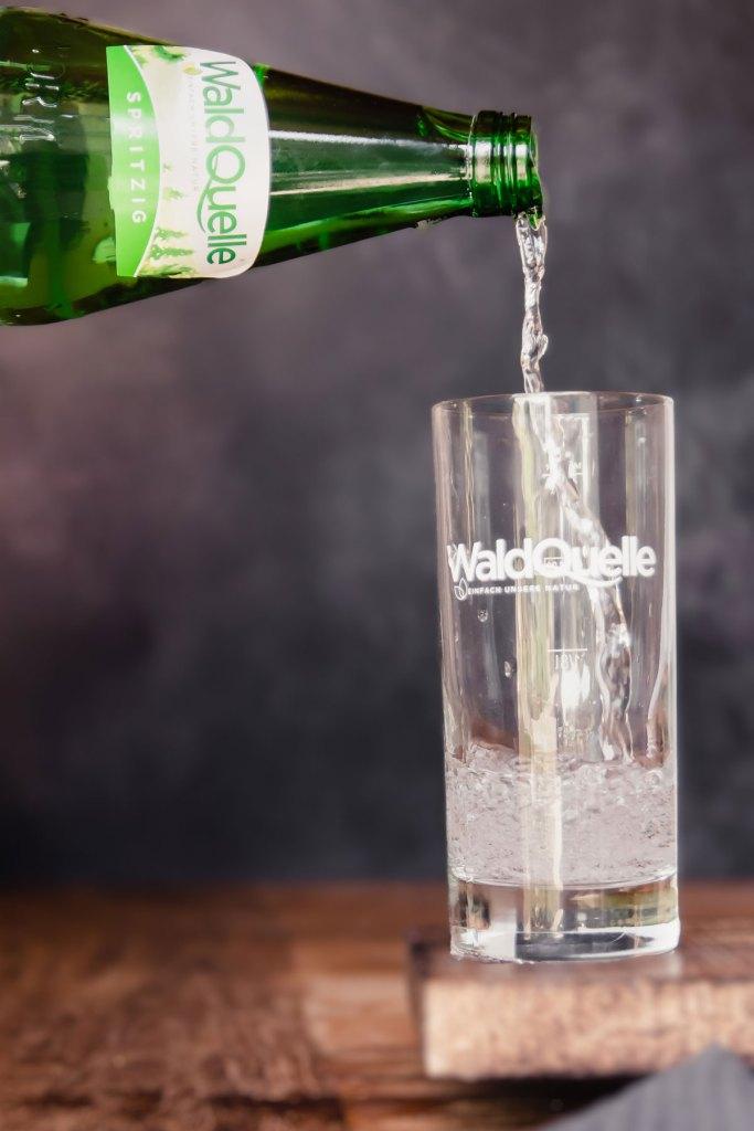 Ein Glas, in das Wasser eingeschenkt wird.