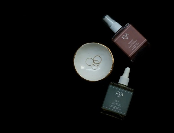 Bottle of Jiya Beauty Earth Aroma Mist and bottle of Jiya Beauty Sky Body Oil on black background adjacent to ring dish with 3 rings