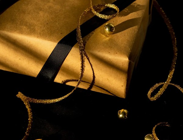 brown paper covered gift box with black and gold ribbon