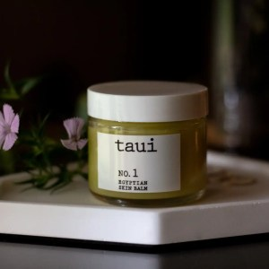 Glass jar of Taui balm on a white tray