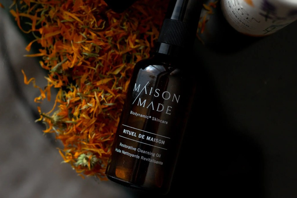 Amber brown bottle of Maison Made Facial Cleansing Oil on table with calendula petals