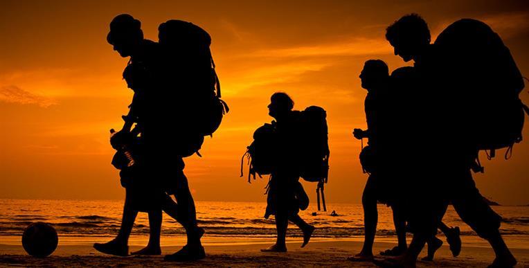 Cinco viajeros con mochilas muy grandes caminando.