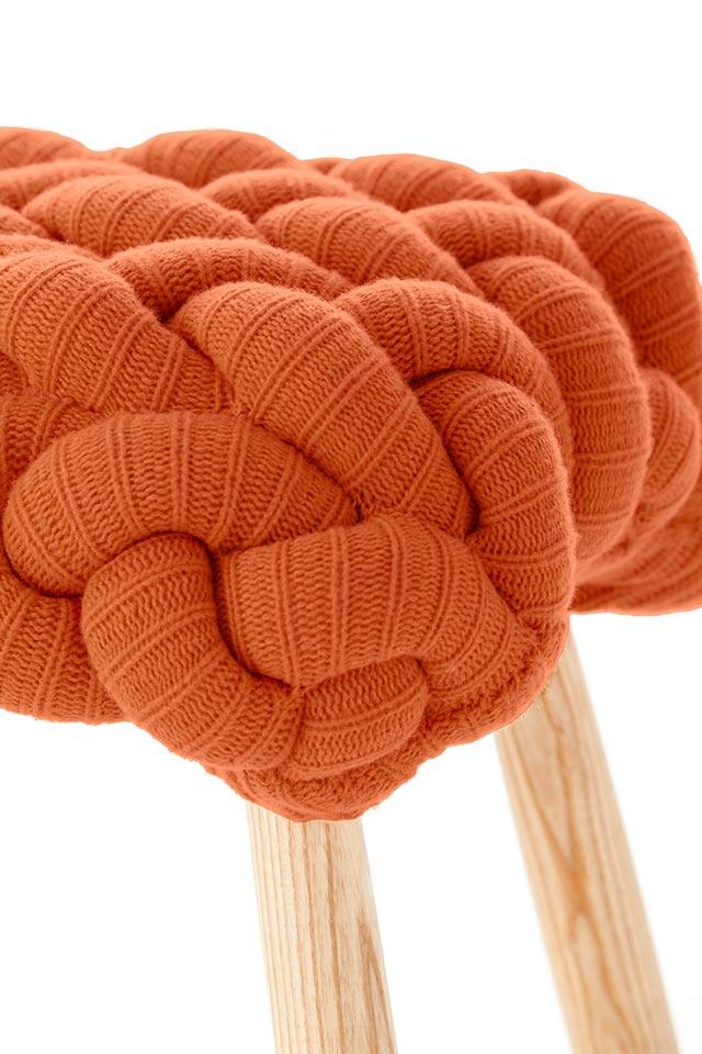 Pouf a maglia colore arancione.