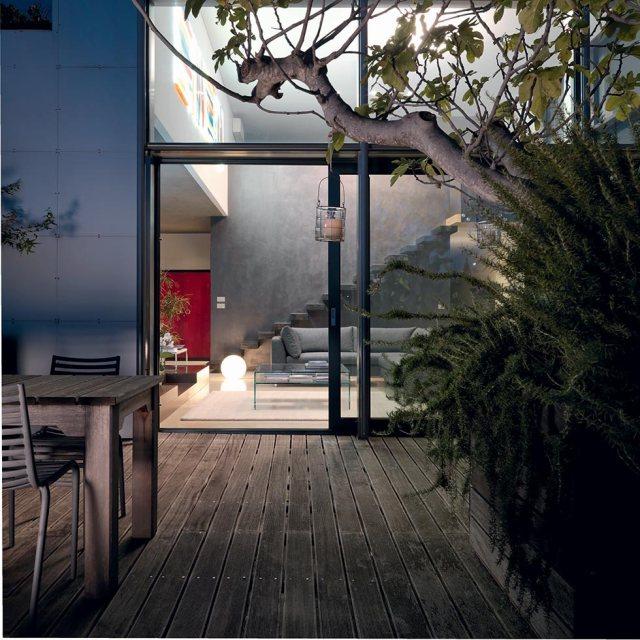 Patio esterno di notte con vista sul soggiorno loft.