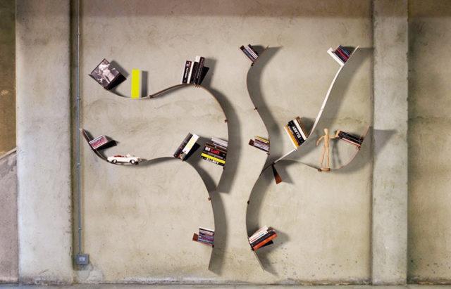 Libreria da parete simile ad un albero con mensole in acciaio flessibile.