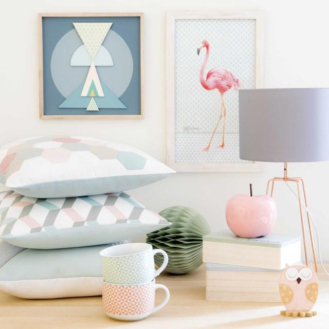 cuscini con motivi geometrici tinte pastello e tazze in primo piano.