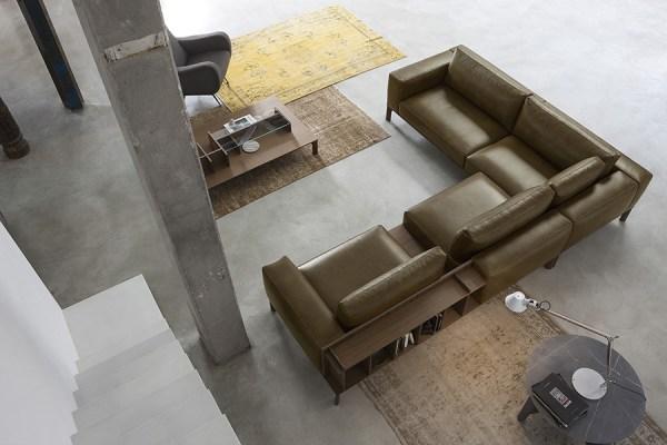 Place di Doimo Salotti - divano in pelle marrone ad angolo con libreria a schienale.