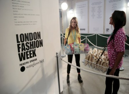 Two members of the catering crew carry trays of popcorn as they wait for guests to arrive during London Fashion Week in London, Britain September 18, 2015. REUTERS/Suzanne Plunkett
