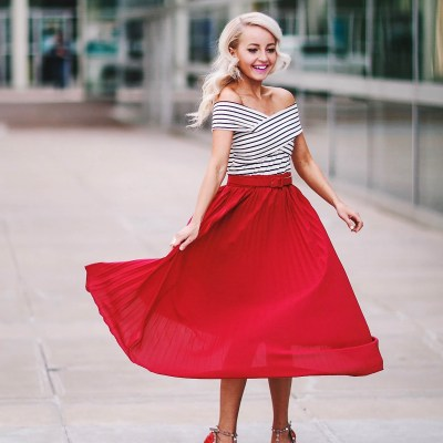 Alena Gidenko of modaprints.com styles a red pleated skirt with an off shoulder stripped top and studded Valentino heels
