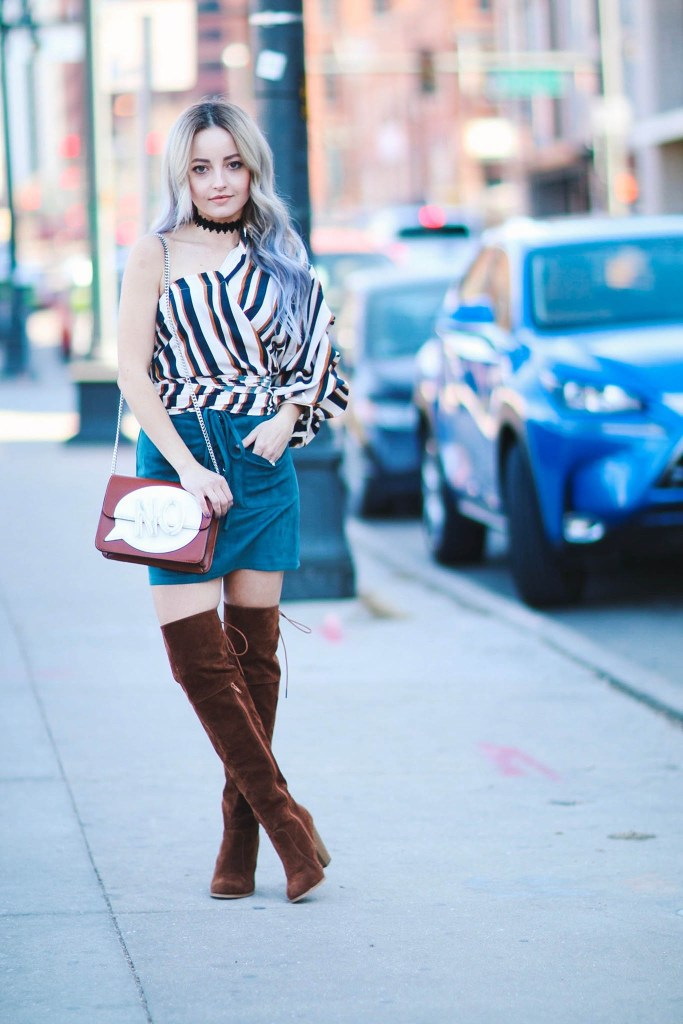 Alena Gidenko of modaprints.com styles a funky off shoulder top with a teal skirt and over the knee tan boots
