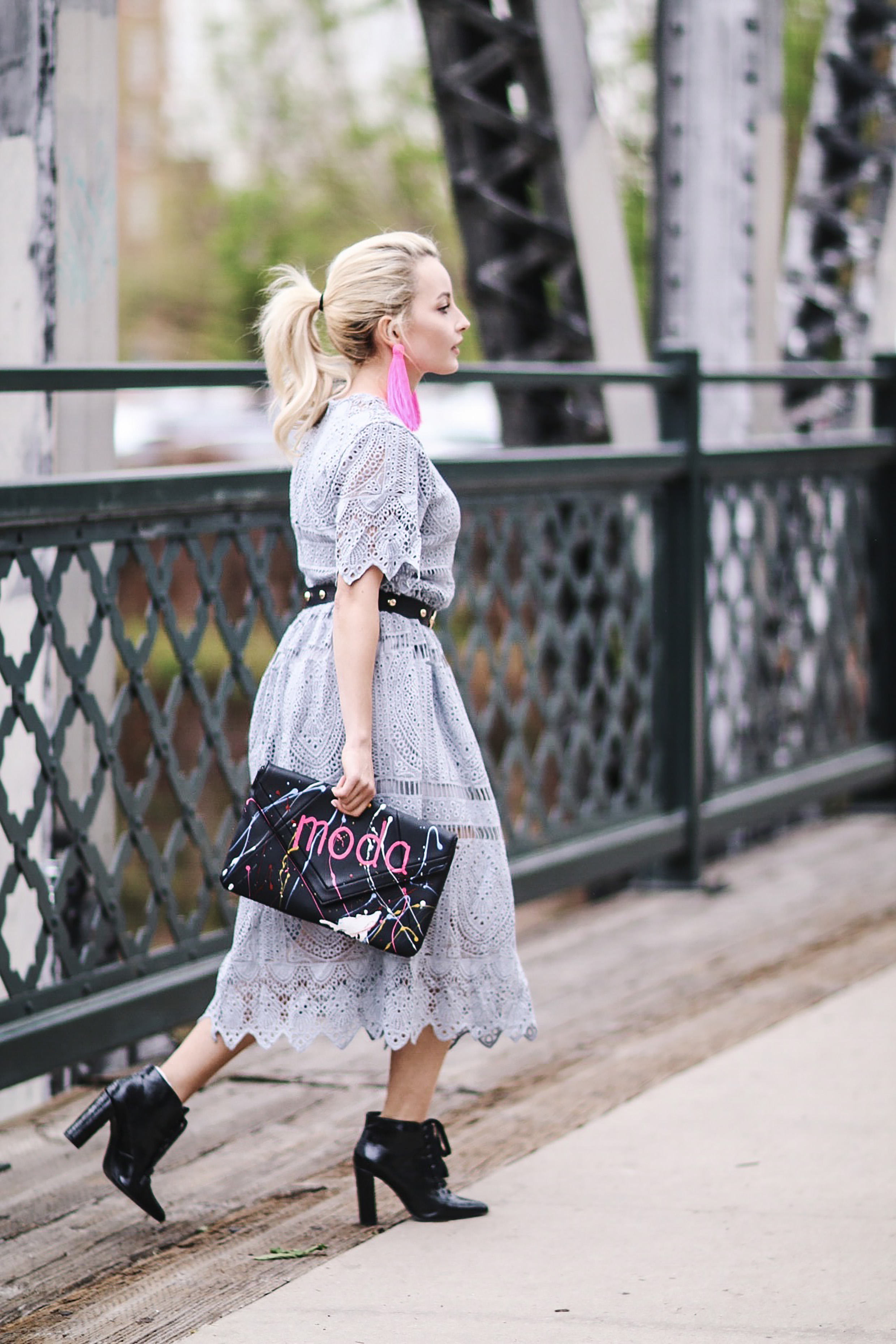Alena Gidenko of modaprints.com styles a lace grey dress with booties and adds a pop of color with earrings and a clutch