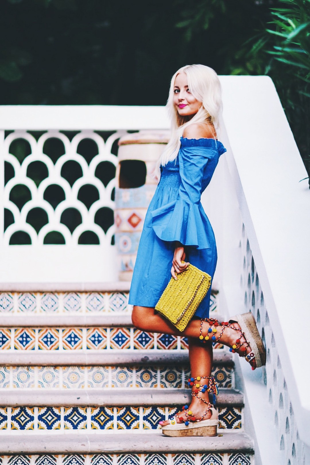 Alena Gidenko of modaprints.com styles a deep blue off the shoulder dress with pom pom sandals for Summer