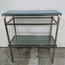 "**ITEM NOW SOLD** Steel/glass two-tier table, designed by Steven Hensel of Studio Steel (no longer in production), c. 1994-96. 26""w x 13""d x 29""h. Orig. List: $1,075. Modele's Price: 550.-"