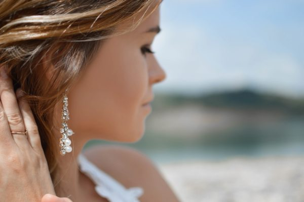 shallow focus photography of woman wearing dangling earrings holding her hair near mountain