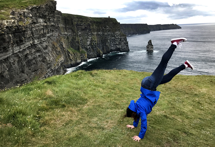 Handstand by the Cliffs of Moher in Ireland in the same pair of pants for 3 days carry-on packing tips