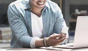 Mann mit Smartphone und Laptop