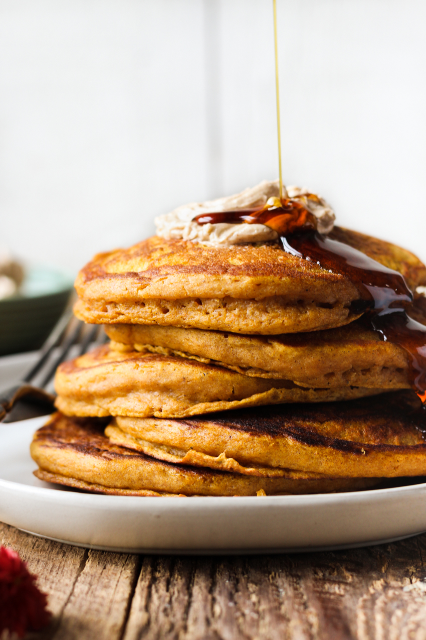 Fluffy pumpkin pancakes with cinnamon honey butter and maple syrup