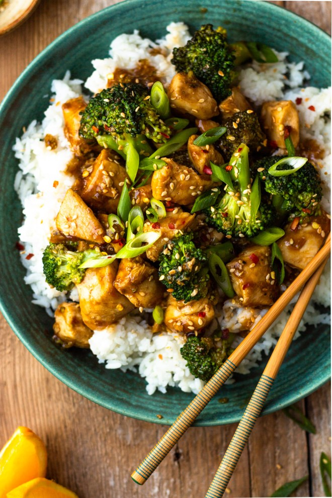 spicy orange chicken and broccoli over rice in a bowl