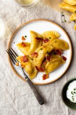 Easy, homemade, tender pasta dough filled with crispy bacon, sharp cheddar cheese and creamy, buttery mashed potatoes. The best comfort food!! Boil the pierogies then sauté in butter and olive oil till golden, delicious perfection. Season with salt and pepper, drizzle with more butter, and top with crumbled bacon and chives.