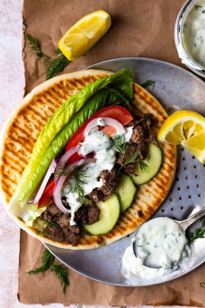 Easy Ground Beef Gyros are so delicious and ready in 30 minutes! Ground beef is perfectly seasoned with a greek spice blend then tucked inside of a soft pita with lots of fresh lettuce, tomato, cucumber, and red onion. Finish the gyro with homemade tzatziki sauce and feta cheese.