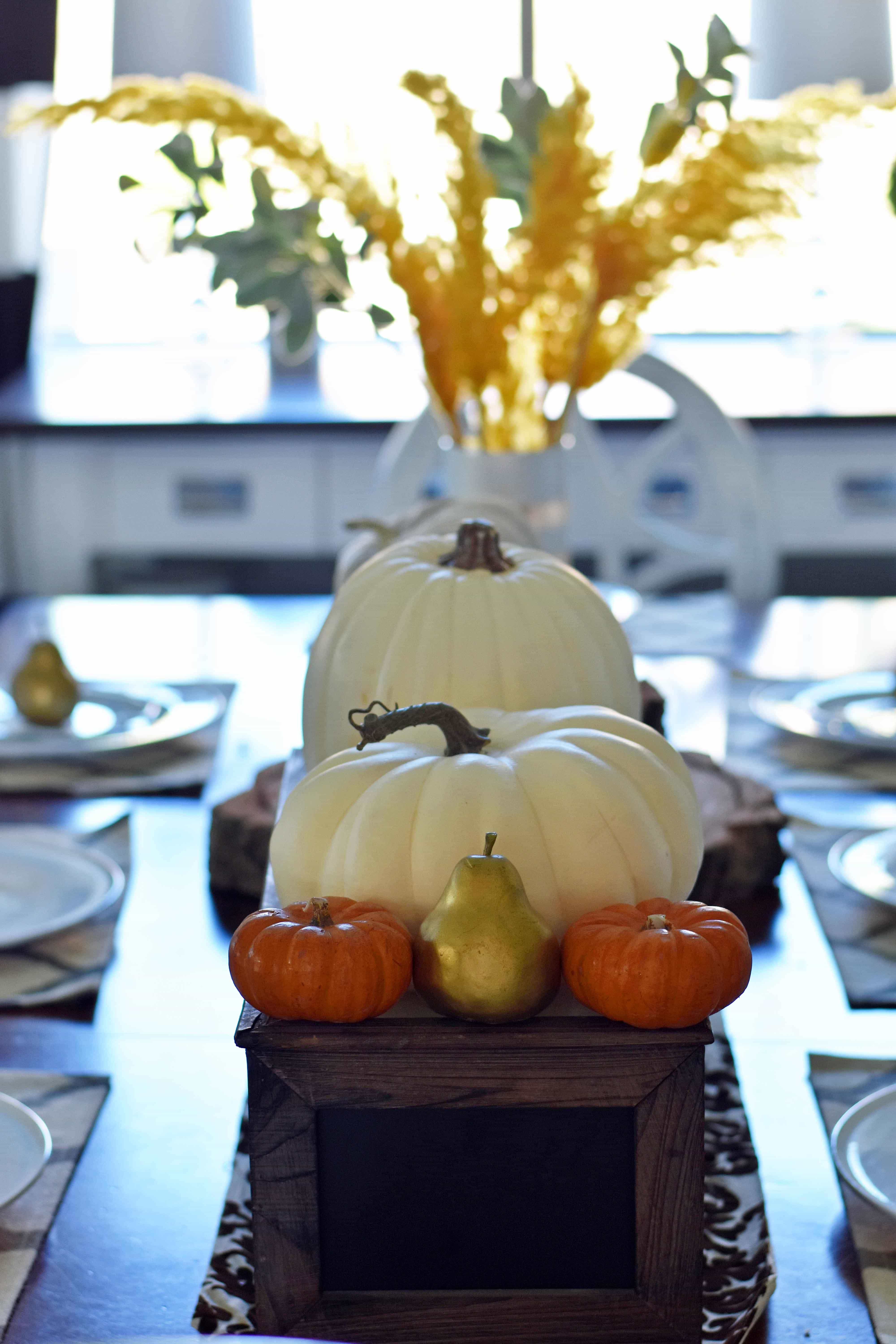 Fall Dining Room Table Decor Ideas. Craspedia Yellow Billy Ball Flowers in vintage vases. White pumpkins in wire baskets. Black and white striped pumpkin. Natural lamps, white entry table, and fall decor. Fixer Upper cotton ball stems. How to decorate your home for Fall.