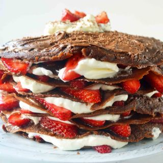 Strawberry Nutella Chocolate Crepe Cake. Layers of chocolate crepes, whipping cream, nutella, and fresh strawberries.