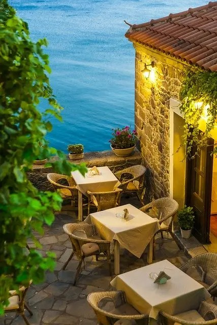The image depicts the outdoors of a stone restaurant with three tables and chairs set up and the sea in the distance.