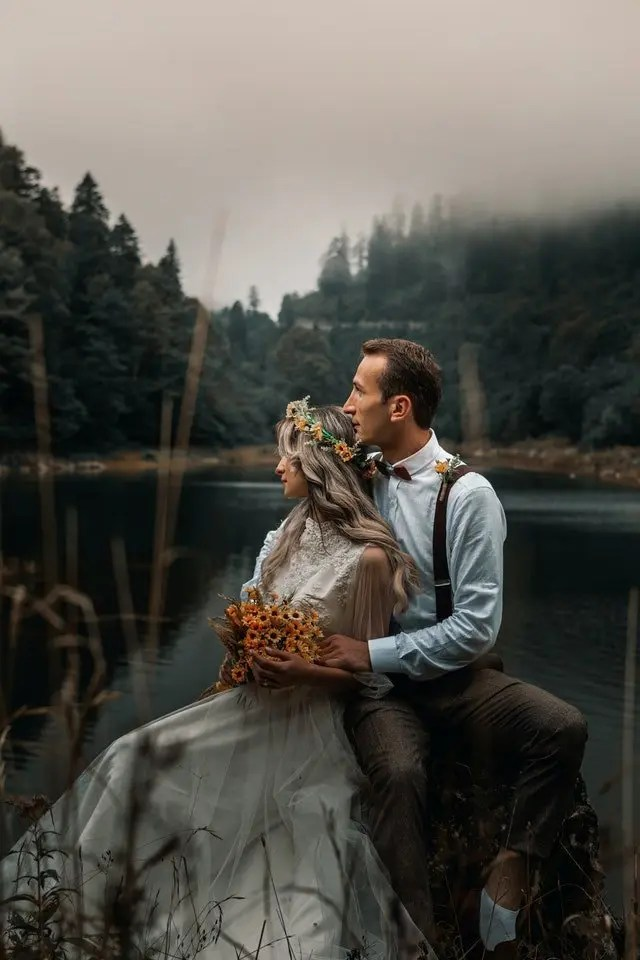 The image depicts a couple sitting together by a lake. They are eloping in Scotland.