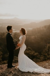 View of a bride and groom standing facing each other with mountains in the distance.