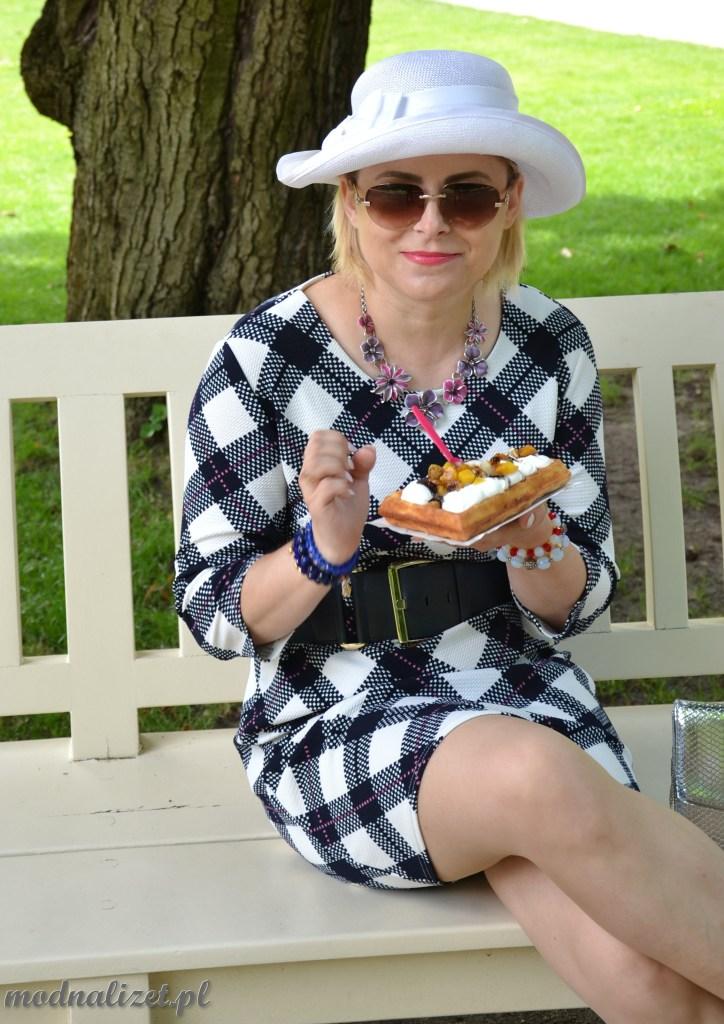 Modna Lizet siedzi na ławeczce i je gofra