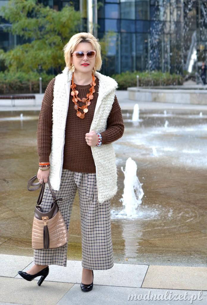 Szerokie spodnie, brązowy sweter i kamizelka kożuszek