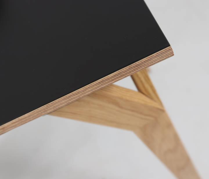 Prikaz površine crnog radnog stola Conform Desk i detalja noge od hrasta