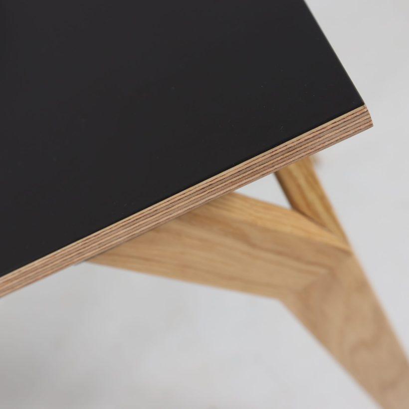Detalj crne površine radnog stola i noge od hrasta