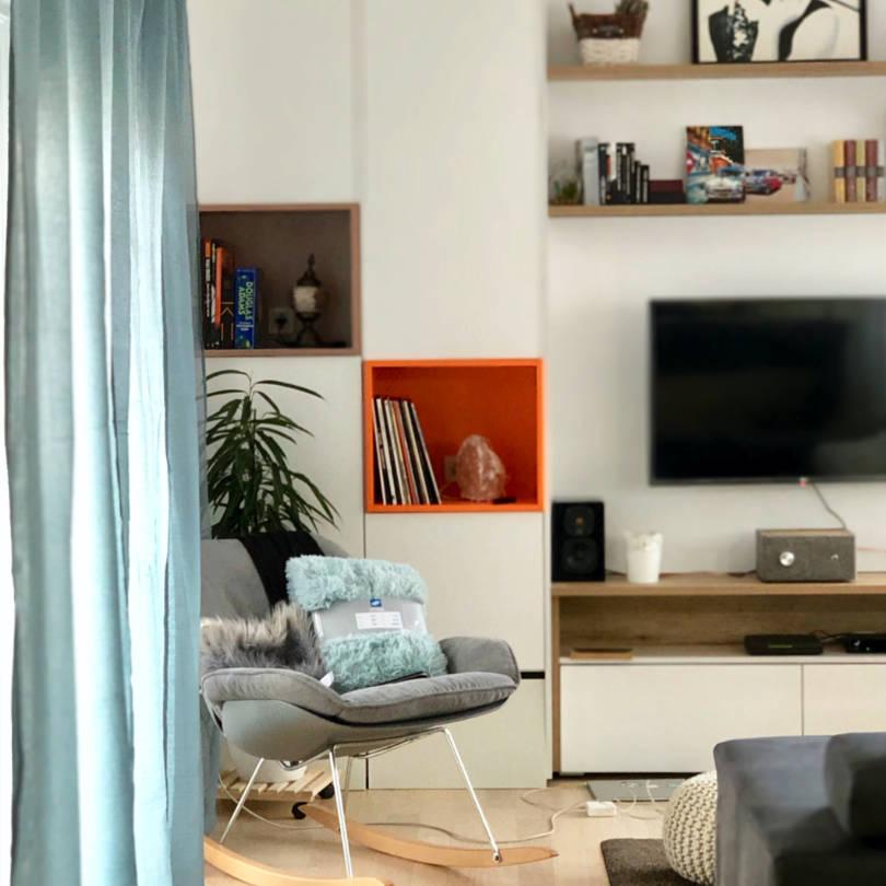 Dnevni boravak po mjeri u kombinaciji bijele boje i drva s narančastim detaljem