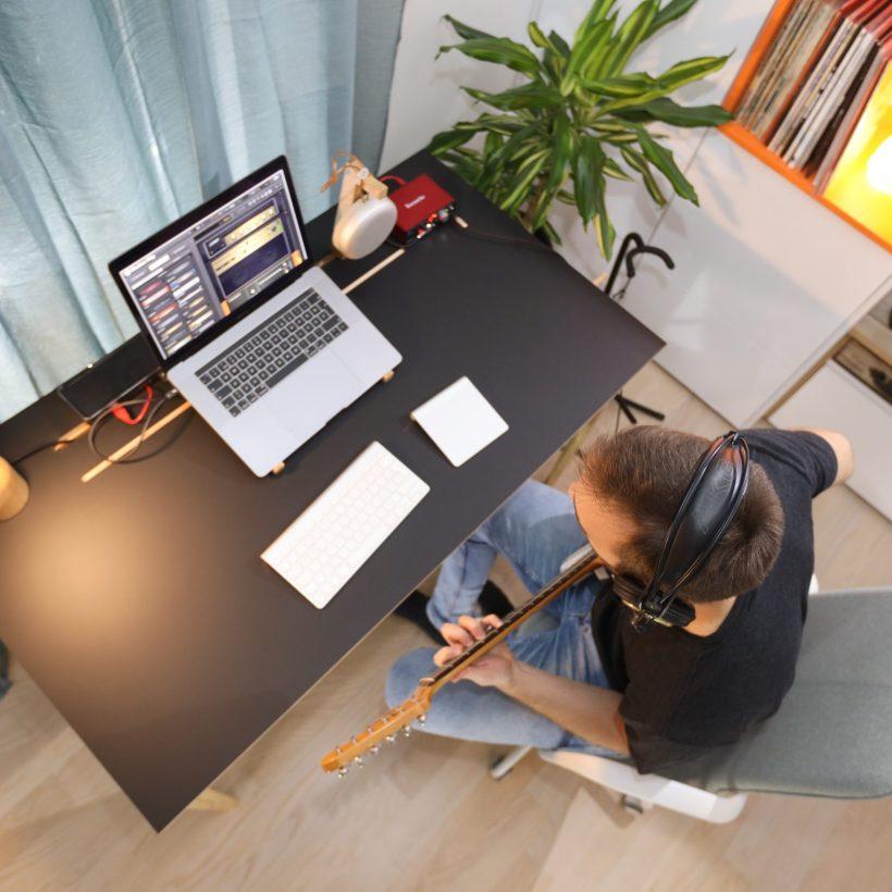 Pogled odozgo na površinu crnog radnog stola Conform Desk i gitarista koji snima glazbu