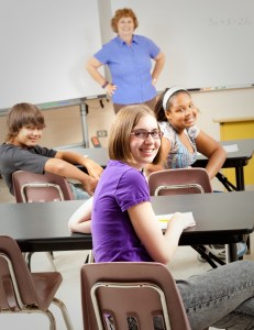 Teacher stands at the front of the room, smiling with her hands on her hips, the middle school students are looking toward the back of the room, smiling at camera.