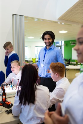Teacher smiling as students work cheerfully on projects