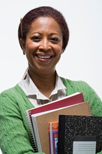 Teacher smiling with an arm load of books.