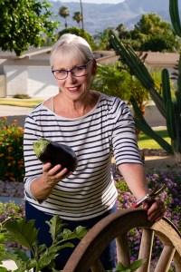 Dietician Elizabeth Kelsey harvests an eggplant from her garden