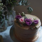 Pear Cake with Salted Caramel Mascarpone Frosting decorated with fresh flowers on a marble table