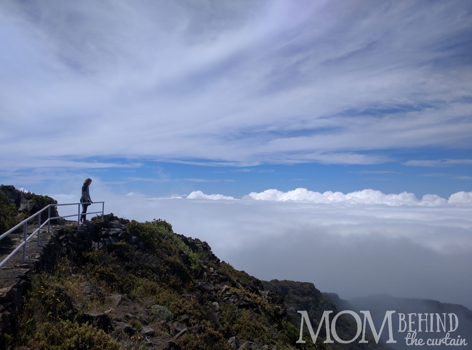 Leleiwi Lookout Maui, girl standing on mountain above the clouds